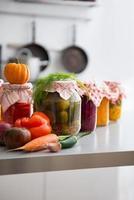 Gläser mit eingelegtem Gemüse auf dem Tisch. Nahansicht foto