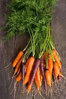 farbige Karotten auf Holzoberfläche foto