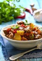 Fleisch mit Gemüse in würziger Tomatensauce gedünstet.