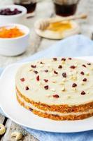 roher veganer Karottenkuchen mit Cashewcreme und getrockneten Preiselbeeren foto