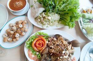 thailändisches Essen im Esstisch - gebrannter Fisch, Chilisauce foto