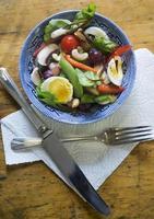 frischer gesunder Sommersalat auf hölzernem Weinlese-Tisch foto