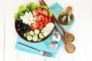 leckerer griechischer Salat mit Gewürzen auf weißem Holzhintergrund