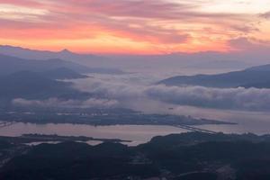 Die Berge sind von Morgennebel und Sonnenaufgang bedeckt foto