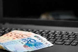 Geld auf der Tastatur des Computers foto