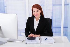 selbstbewusste Geschäftsfrau, die Steuern berechnet foto