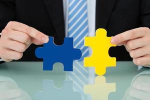 Geschäftsmann, der Puzzleteile verbindet