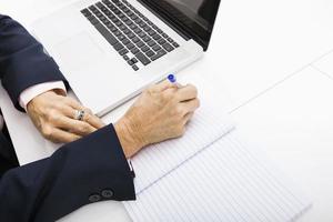 Geschäftsfrau mit Laptop, der in Notizbuch auf Schreibtisch schreibt foto