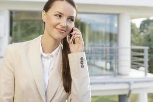 schöne Geschäftsfrau, die Handy gegen Bürogebäude beantwortet foto