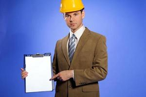 Porträt des Geschäftsmannes im Helm, der auf Zwischenablage zeigt foto