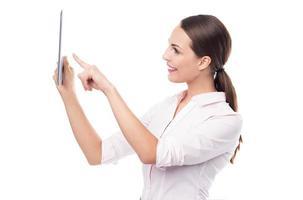 Frau zeigt auf digitales Tablet foto