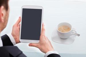 Geschäftsmann, der digitales Tablett im Büro hält foto