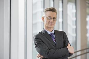 Porträt des selbstbewussten Geschäftsmannes, der Arme im Amt verschränkt foto