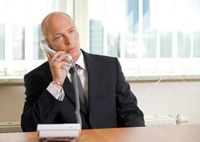 Geschäftsmann, der am Telefon im Büro spricht foto