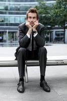junger kaukasischer Geschäftsmann, der auf Bank sitzt foto