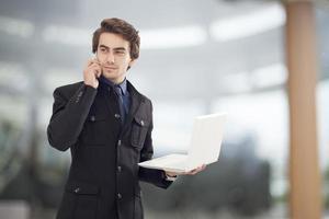 Porträt des jungen Geschäftsmannes, der Laptop hält foto