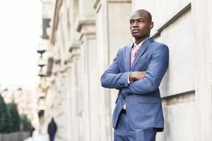 schöner schwarzer Mann, der Anzug im städtischen Hintergrund trägt foto