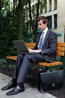 junger kaukasischer Geschäftsmann, der seinen Laptop im Park benutzt