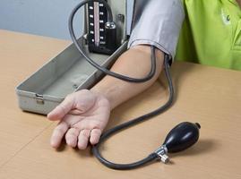 Überprüfung des Blutdrucks eines Patienten foto