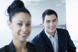 Porträt von zwei Geschäftsleuten, die lächeln und Kamera betrachten foto