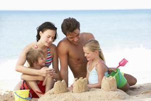 Porträt der Familie, die Strandurlaub genießt foto