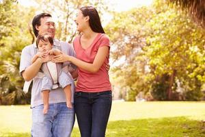 Familie mit Baby in der Trage, die durch Park geht foto