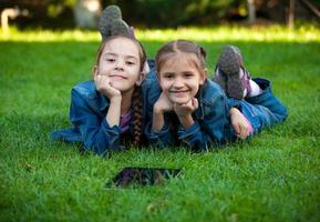 Porträt von zwei kleinen Mädchen, die auf Gras mit Tablette liegen