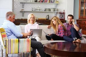 Eltern mit erwachsenen Nachkommen, die zu Hause digitale Geräte verwenden foto