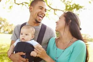 Familie mit kleinem Sohn im Träger, der durch Park geht foto