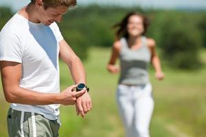 Sommer Joggen - junger Mann mit Stoppuhr Messzeit