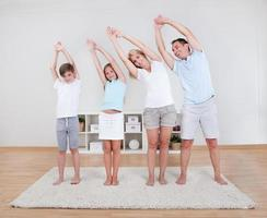 Familie macht Dehnübungen auf dem Teppich foto