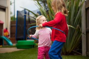 zwei kleine Mädchen in einem Hula Hoop foto