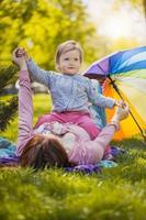 glückliche Mutter und Baby liegen auf der Wiese