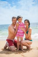 Porträt eines jungen Paares in Badeanzügen mit ihrer Tochter