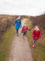 Frau und zwei kleine Kinder, die durch Dünenlandschaft gehen foto