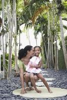 Mutter kauert mit Tochter auf Trittstein