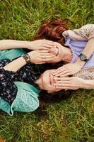 zwei fröhliche Schwestern, die im Gras liegen foto