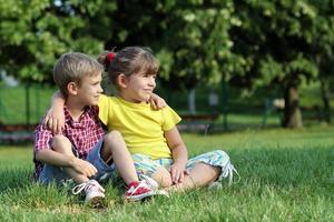 Junge und kleines Mädchen sitzen auf Gras im Park foto