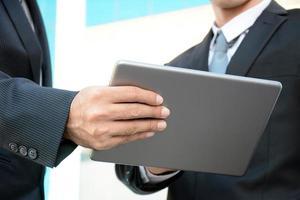 zwei Geschäftsleute, die Tablet-Computer betrachten