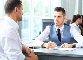 glückliche Geschäftsleute, die über das Treffen im Büro sprechen foto
