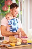 Vater hält Baby und macht Snack, während er Laptop benutzt foto