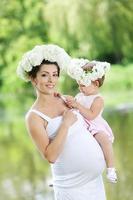 schwangere Mutter und ihre Tochter haben Spaß im Freien foto