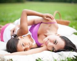 Mutter und Tochter liegen auf Picknickdecke foto