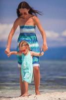 kleines Mädchen und junge Mutter am tropischen Strand foto