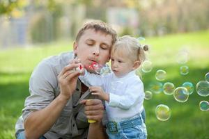 Ein Vater und seine Tochter blasen Blasen in einem Park foto