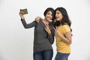 zwei hübsche junge Frauen, die Selfie mit Handy nehmen foto
