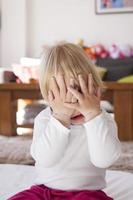 Babyhände bedecken ihr Gesicht foto