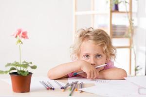 süßes kleines Mädchen, das mit Stiften zeichnet foto