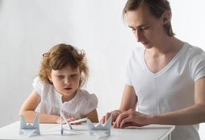 kleines Mädchen mit ihrem älteren Bruder macht Papierkräne foto