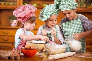 drei kleine Kinder, die Zutaten für Kekse in der Küche vorbereiten foto